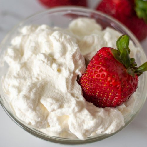 whipped cream in a bowl with a strawberry