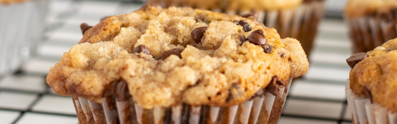 chocolate chip banana muffin with crumb topping on cookie rack